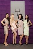 Quatro meninas bonitas em ternos vestindo do estilo da forma Fotografia de Stock Royalty Free