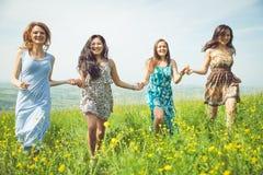 Quatro meninas que correm nos campos Fotografia de Stock Royalty Free