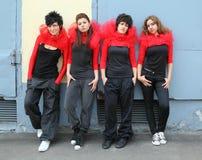 Quatro meninas que estão e que inclinam-se na parede imagem de stock