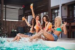 Quatro meninas que têm o divertimento e que bebem cocktail na piscina imagem de stock