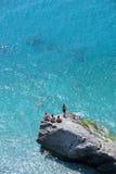 Quatro meninos novos que sentam as rochas que prestam atenção ao dia vão perto Imagens de Stock Royalty Free