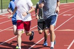 Quatro meninos que correm em um grupo em uma trilha Fotografia de Stock Royalty Free