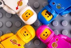 Quatro minifigures do astronauta de Lego no fundo cinzento da placa de base foto de stock royalty free