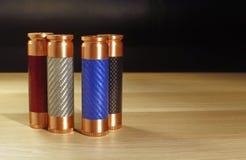 Quatro mods mecânicos vermelhos, azuis, brancos e pretos coloridos para vaping o cigarro eletrônico na superfície de madeira em v imagens de stock