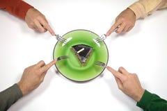 Quatro mãos um bolo Fotografia de Stock
