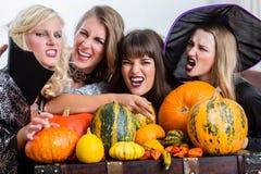 Quatro mulheres alegres que comemoram Dia das Bruxas junto durante o traje Fotografia de Stock
