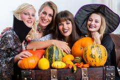 Quatro mulheres alegres que comemoram Dia das Bruxas junto durante o traje Fotos de Stock Royalty Free