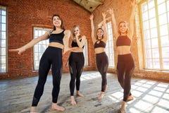 Quatro mulheres bonitas no sportswear que levanta em várias poses da dança em um estúdio do sótão nas grandes janelas, rindo e fa fotos de stock royalty free