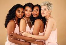Quatro mulheres bonitas que abraçam-se em um estúdio foto de stock royalty free