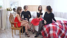 Quatro mulheres bonitas têm negociações da bisbolhetice e discutem problemas ao sentar-se na cama vídeos de arquivo