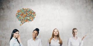 Quatro mulheres com bolhas do discurso na sala concreta Foto de Stock Royalty Free