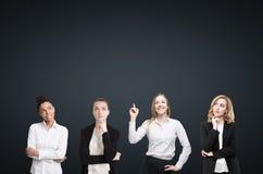 Quatro mulheres conceituam perto da parede preta fotografia de stock royalty free