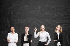 Quatro mulheres conceituam perto do quadro-negro foto de stock