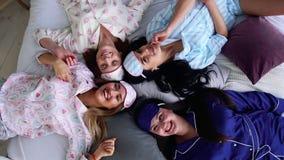 Quatro mulheres de sorriso nos pijamas encontram-se na cama e olham-se diretamente na câmera em um partido de pijama bridesmaid video estoque