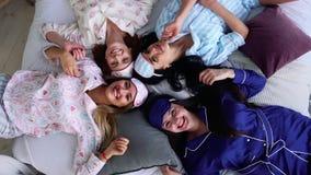 Quatro mulheres de sorriso nos pijamas encontram-se na cama e olham-se diretamente na câmera em um partido de pijama bridesmaid vídeos de arquivo