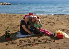 Quatro mulheres do Natal na praia da areia Fotos de Stock Royalty Free