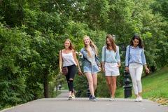 Quatro mulheres novas atrativas dos amigos que falam e que andam junto na passagem imagens de stock royalty free