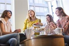 Quatro mulheres que comem o lanche imagem de stock