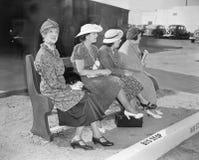 Quatro mulheres que sentam-se em um banco que espera o ônibus (todas as pessoas descritas não são umas vivas mais longo e nenhuma fotos de stock royalty free
