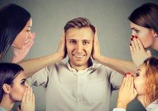 Quatro mulheres que sussurram a bisbolhetice a um homem que cubra as orelhas que ignoram todo o ruído circunvizinho foto de stock royalty free