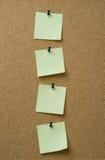 Quatro notas amarelas fixadas ao fundo da cortiça imagens de stock royalty free