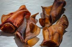 Quatro orelhas da carne secada na luz solar brilhante em um fundo natural branco Foco seletivo Macro fotografia de stock