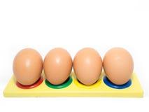 Quatro ovos em furos coloridos Fotos de Stock