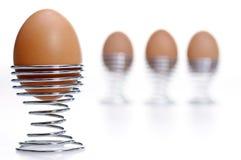 Quatro ovos em uns copos do metal Fotografia de Stock