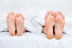 Quatro pés em uma cama Imagens de Stock
