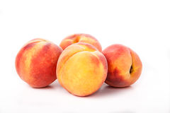 Quatro pêssegos no branco Fotografia de Stock