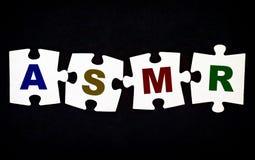 Quatro partes de enigma com letras ASMR no fundo preto fotografia de stock royalty free
