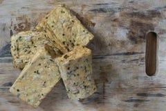 Quatro partes de tofu com ervas em uma placa de madeira foto de stock