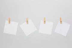 Quatro notas brancas em Clotheswire Imagem de Stock