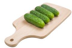 Quatro pepinos verdes frescos na placa de estaca Imagens de Stock