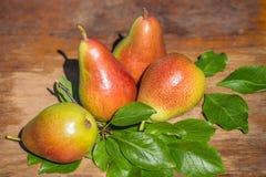 Quatro peras vermelhas e verdes maduras com folhas verdes em um close up de madeira da tabela Imagens de Stock