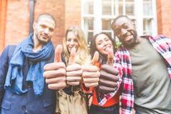 Quatro pessoas com as afiliações étnicas diferentes que mostram os polegares acima fotografia de stock royalty free