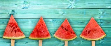 Quatro picolés da fatia da melancia no fundo de madeira azul panorâmico, conceito do fruto fresco imagens de stock royalty free