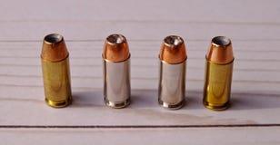 Quatro pontos da cavidade de 40 calibres alinharam em uma terra traseira de madeira branca imagens de stock