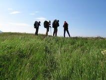 Quatro povos no backpacking Imagem de Stock Royalty Free