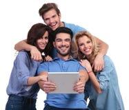 Quatro povos ocasionais de riso que leem em uma tabuleta acolchoam o computador Imagem de Stock Royalty Free