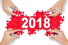 Quatro povos que arranjam o enigma com número 2018 Imagens de Stock Royalty Free