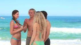 Quatro povos que conversam junto na praia video estoque