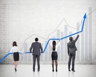 Quatro povos que guardam um gráfico foto de stock royalty free