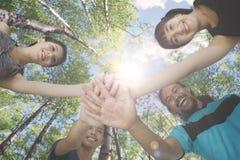 Quatro povos que juntam-se a suas mãos no parque Fotografia de Stock
