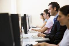 Quatro povos que sentam-se na dactilografia do quarto de computador Imagem de Stock Royalty Free