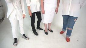 Quatro povos vestiram-se nas calças de brim, vestido, calças do whete que estão em um assoalho Isolado sobre o fundo branco video estoque