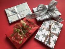Quatro presentes envolvidos luxuosos do Natal em um fundo vermelho imagem de stock