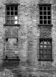 Quatro quebrados e bricked acima das janelas em um derelict abandonaram a casa imagens de stock