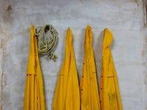 Quatro revestimentos de chuva amarelos e um roap Imagem de Stock Royalty Free