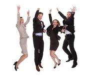 Quatro sócios comerciais que saltam para a alegria fotos de stock